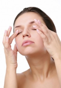 Young woman pushes with fingers on closed eyes. Isolated over white.