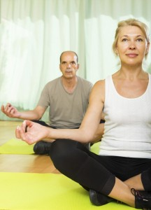 Elderly couple having yoga at home