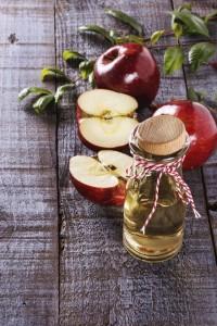 Apple cider vinegar and apples over white wooden background